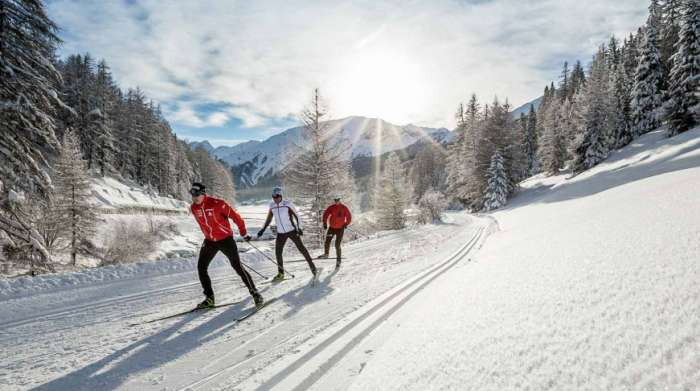 Three people cross country skiing
