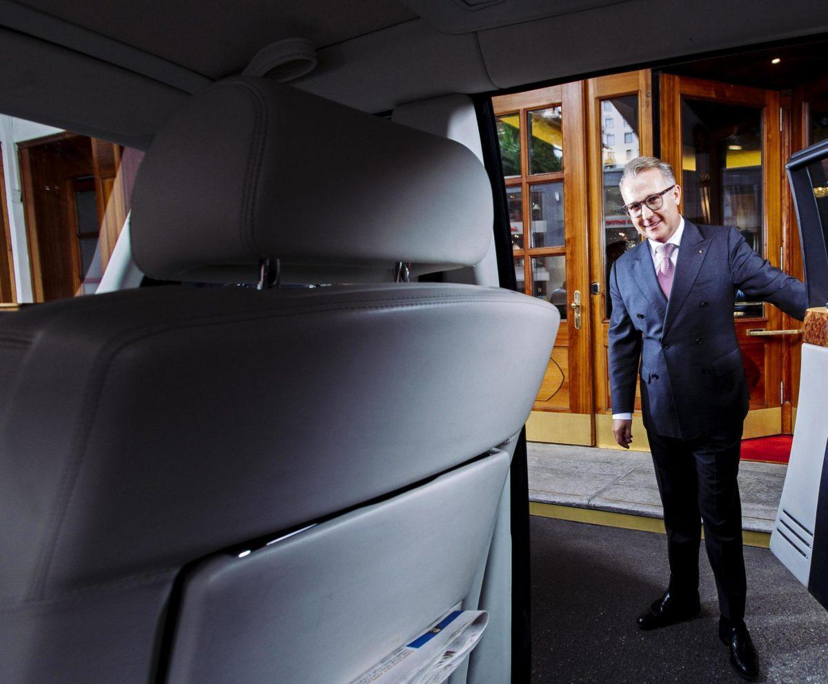 A concierge opening car door