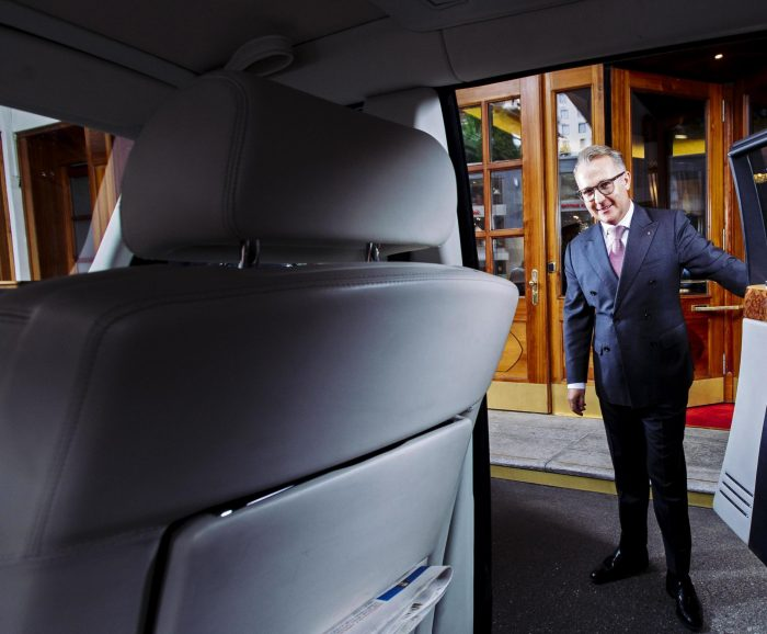 A concierge opening car door