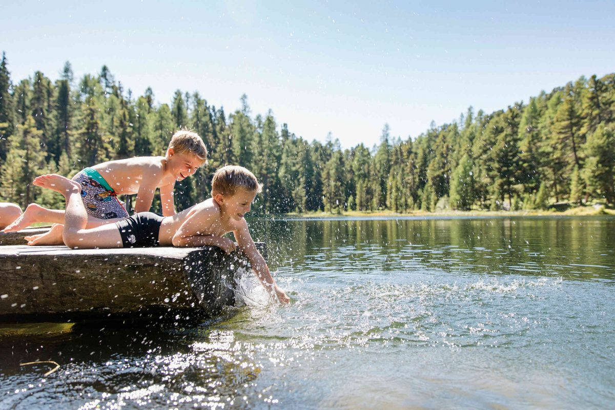 Children enjoy relaxing by the lakes in the Engadin